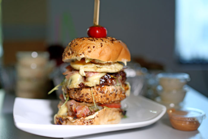"HUNGER-TAMER DOUBLE BURGER |Topelt-veisepihv, kukkel, krõbe peekon, ""garlic mayo"", praemuna, ""Swiss cheese"", tomat, karamelliseeritud sibul, kurgi-tilli relish, bbq kaste, sibularõngad, ruccola, kirsspaprika, coleslaw"