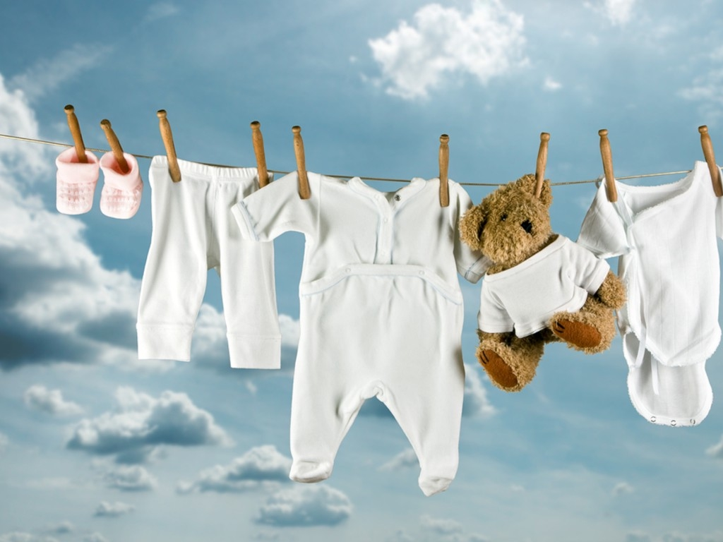 Cute_teddy_bear_hanging_outside_between_baby_laundry